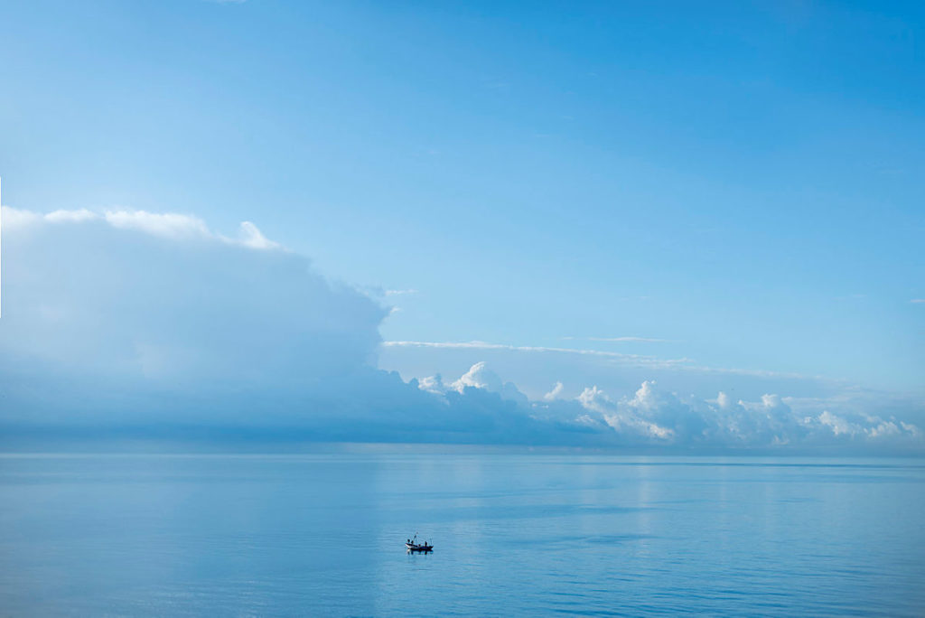 hav med horisont full av hvite skyer